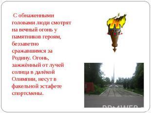 С обнаженными головами люди смотрят на вечный огонь у памятников героям, беззаве