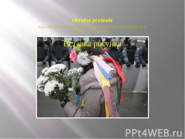 Ukraine protests A pro-EU activist offers flowers to police officers at the presidential office in Kiev, on December 8.